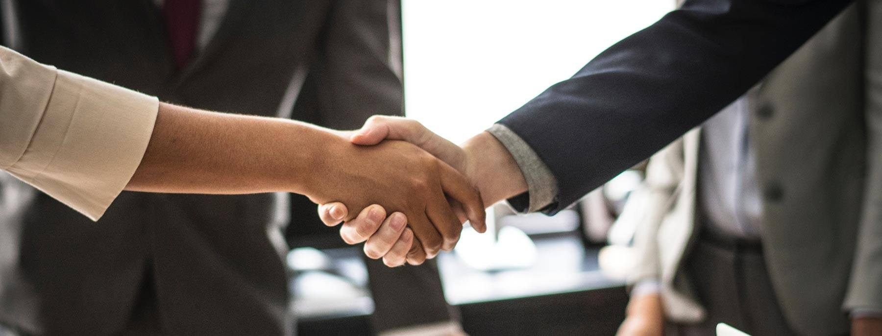 a business man and woman shaking hands in agreement