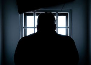 man's silhouette standing in front of a jailhouse window